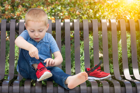 Young Boy Sitting On A Bench Putting On His Shoes At The Park. Imagens