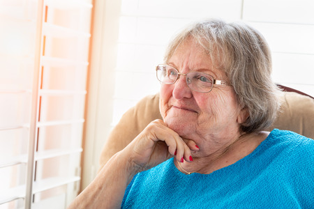 Content Senior Woman Gazing Out of Her Window. Stock Photo