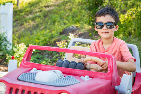 Young Mixed Race Chinese and Caucasian Boy Wearing Sunglasses Playing In Toy Car Stock fotó