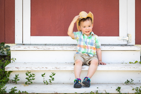 Young Mixed Race Chinese and Caucasian Boy Wearing Cowboy Hat Relaxing On The Steps Stock fotó