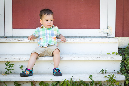 Young Mixed Race Chinese and Caucasian Boy Relaxing On The Steps Stock fotó
