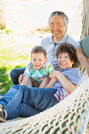 Chinese Grandparents In Hammock with Mixed Race Child.
