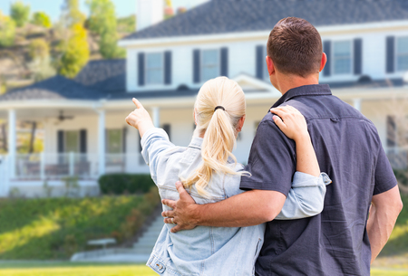 Young Adult Couple Facing and Pointing to Front of House. Stock Photo