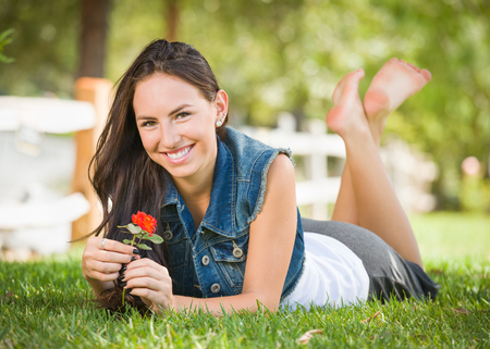 Attractive Mixed Race Girl Portrait Laying in Grass Outdoors with Flower.