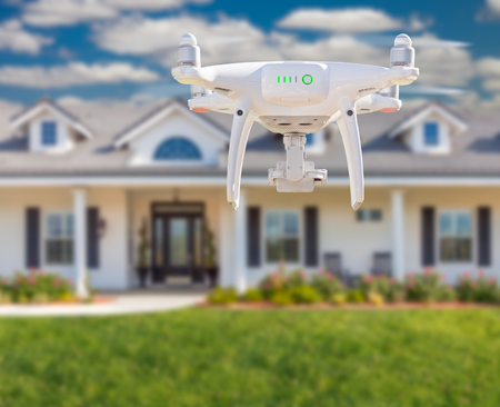 Back of Unmanned Aircraft System (UAV) Quadcopter Drone Flying In Front of House. Stock Photo