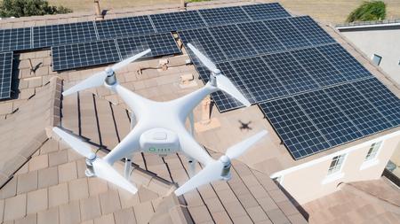 UAV-Drohne, die Sonnenkollektoren auf großem Haus inspiziert. Standard-Bild