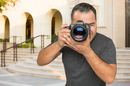 Hispanic Young Male Photographer With DSLR Camera Outdoors.