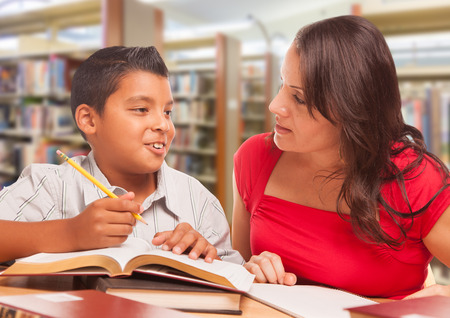 Hispanic Young Boy and Famle Adult Studying At Library. Imagens