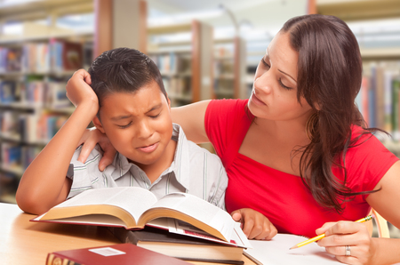 Upset Hispanic Young Boy and Famle Adult Studying At Library.