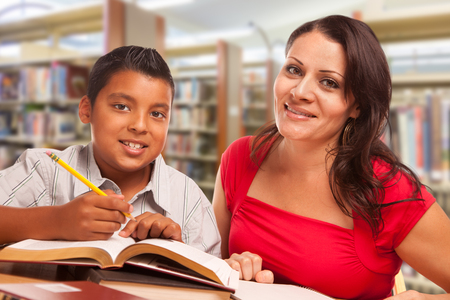 Hispanic Young Boy and Famle Adult Studying At Library. Stock Photo
