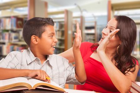 Niño hispano y Famle Adult High Five Whilte estudiando en la biblioteca. Foto de archivo
