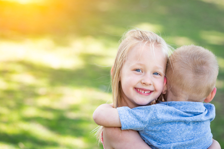Young Brother and Sister Hugging At The Park.