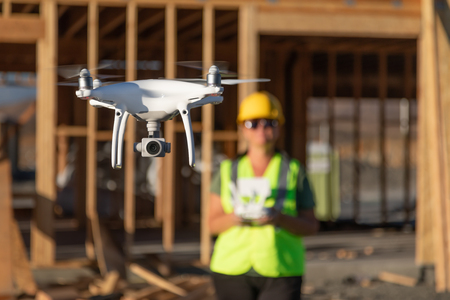 Female Pilot Flies Drone Quadcopter Inspecting Construction Site.
