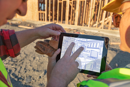 Male and Female Construction Workers Reviewing Kitchen Drawing on Computer Pad at Construction Site. Standard-Bild - 108802414