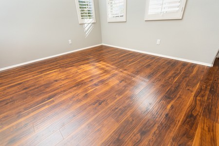 Newly Installed Brown Laminate Flooring and Baseboards in Home. 스톡 콘텐츠
