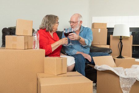 Senior Adult Couple Toasting Wine Glasses Surrounded By Moving Boxes.