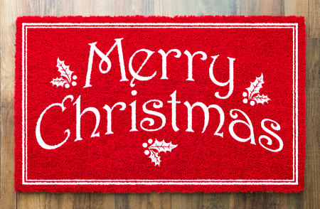 Merry Christmas Red Welcome Mat On Wood Floor Background. Imagens