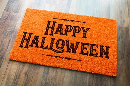 Happy Halloween Orange Welcome Mat On Wood Floor Background. Archivio Fotografico