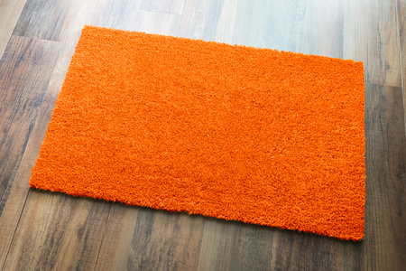 Blank Orange Welcome Mat On Wood Floor Background Ready For Your Own Text.