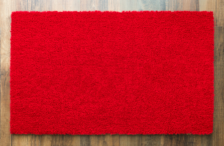 Blank Red Welcome Mat On Wood Floor Background Ready For Your Own Text.