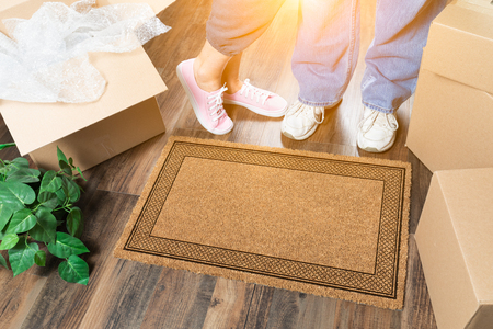 Man and Woman Standing Near Blank Welcome Mat, Moving Boxes and Plant.