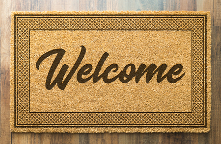 Welcome Mat On A Wood Floor Background.