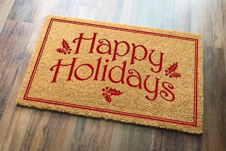 Happy Holidays Christmas Tad Welcome Mat On Wood Floor Background. Stockfoto