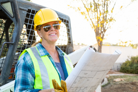 Smiling Female Worker Holding Technical Blueprints Near Small Bulldozer At Constrcution Site Stockfoto