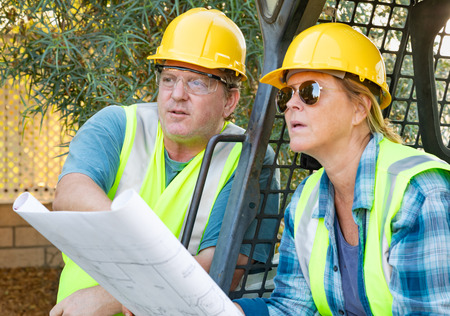 Male and Female Workers With Technical Blueprints Talking at Construction Site
