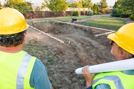 Male and Female Workers Overlooking Pool Construction Site Stockfoto