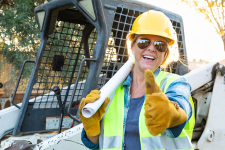 Smiling Female Worker With Thumbs Up and Technical Blueprints Near Small Bulldozer At Constrcution Site