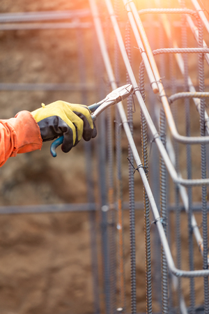 Worker Securing Steel Rebar Framing With Wire Plier Cutter Tool At Construction Site.