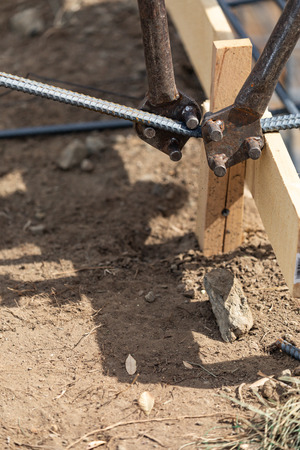 Worker Using Tools To Bend Steel Rebar At Construction Site.
