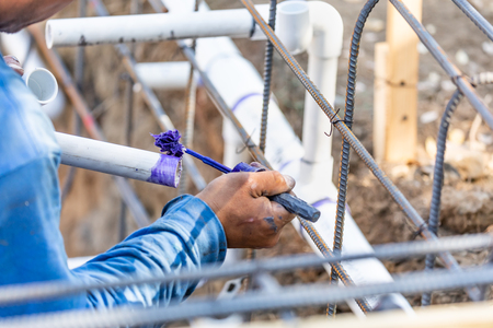 Plumber Applying Pipe Cleaner, Primer and Glue to PVC Pipe At Construction Site.
