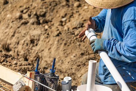 Plumber Applying Glue To PVC Pipe At Construction Site.
