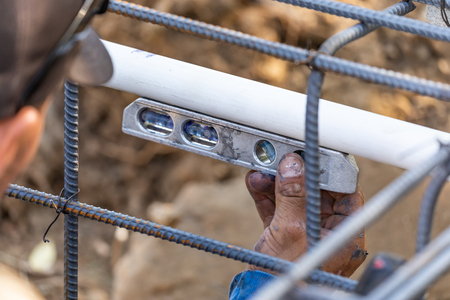 Plumber Using Level While Installing PVC Pipe At Construction Site. Stock Photo