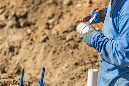 Plumber Applying PTFE Tape To PVC Pipe At Construction Site.