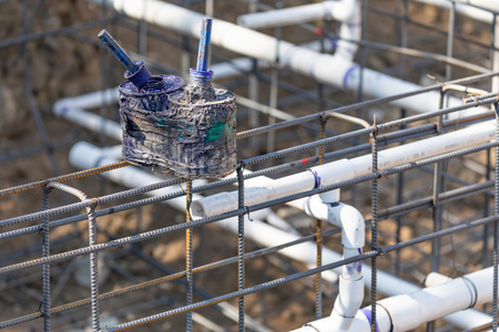 Newly Installed PVC Plumbing Pipes and Steel Rebar Configuration At Construction Site.