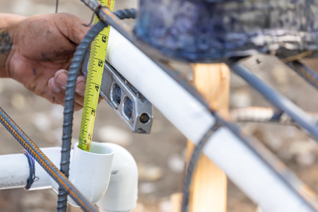Plumber Using Level And Tape Measure While Installing PVC Pipe At Construction Site.