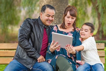 Caucasian Mother and Hispanic Father Using Computer Tablet With Mixed Race Son Outdoors.