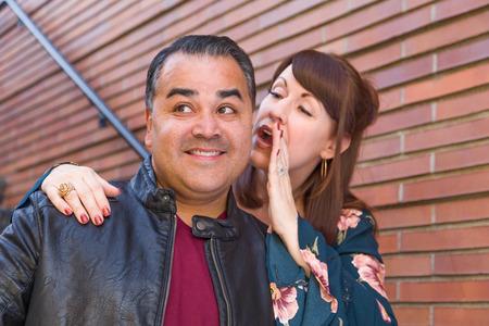 Caucasian Woman Whispering Secret to Hispanic Man.