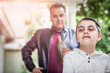 Afraid and Bruised Mixed Race Boy In Front of Angry Man Holding Bottle of Alcohol. Stock Photo