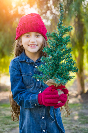 Cute Mixed Race Young Girl Wearing Red Knit Cap and Mittens Holding Small Christmas Tree Outdoors. Imagens