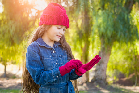 Cute Mixed Race Young Girl Wearing Red Knit Cap Putting On Mittens Outdoors.