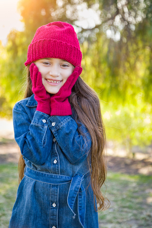 Cute Mixed Race Young Girl Wearing Red Knit Cap and Mittens Outdoors. Stock Photo