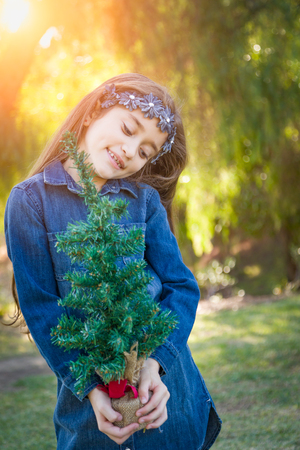 Cute Mixed Race Young Girl Holding Small Christmas Tree Outdoors. Stock Photo