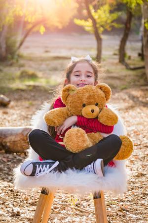Cute Young Mixed Race Girl Hugging Teddy Bear Outdoors.
