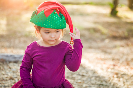 Cute Mixed Race Young Baby Girl Having Fun Wearing Christmas Hat Outdoors.