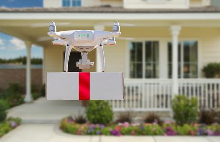 Drone quadrirotor du système d'aéronef sans pilote (UAV) livrant une boîte avec un ruban rouge à la maison Banque d'images