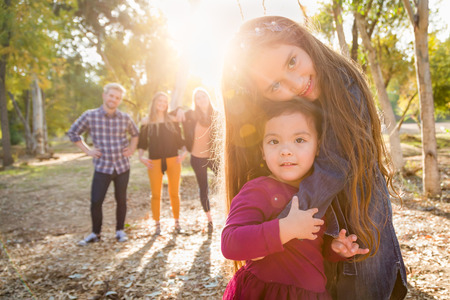 Mixed Race Young Girl Sisters Outdoors with Family Behind. Stock Photo